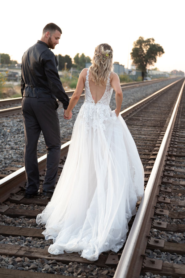 bride and groom walking on railroad tracks while holding hands